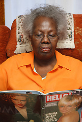 Elderly lady looking at magazine.