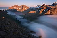 Summer fog flows over mountain pass towards Vindstad, Moskenesøy, Lofoten Islands, Norway