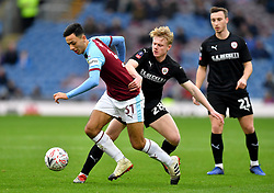 Burnley's Dwight McNeil (left) and Barnsley's Ben Williams (right) battle for the ball during the Emirates FA Cup, third round match at Turf Moor, Burnley.
