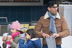 *Note to editors : please note minors in images pixilate where appropriate*  © Licensed to London News Pictures. 31/01/2021. London, UK. Chancellor of the Exchequer Rishi Sunak folds a scarf after buying hot beverages in a Central London Park during a walk with his wife, Akshata Murthy their two children. Photo credit: George Cracknell Wright/LNP
