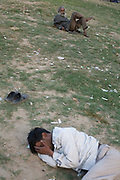 A homeless mentally ill man sits in a park near the banks of the Yamuna River whilst another sleeps, Delhi, India<br /> <br /> It is estimated that around than 150000 people - more than one percent of the city - is homeless and, with constant migration this is increasing on a daily basis. The incidence of mental illness amongst this group is very high. Delhi has little formal provision to deal with such a situation. Countrywide there are no more than 400 registered psychiatrists. Delhi, India