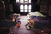 Nalim and Namgay's family sleeping arrangements in their home in Shingkhey, Bhutan. The family of subsistence farmers lives in a 3-story rammed-earth house in the hillside village of Shingkhey, Bhutan. From Peter Menzel's Material World Project.
