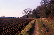 A913H2 Country land and brown furrows of ploughed land in winter field Butley, Suffolk, England