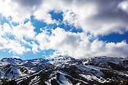 High Atlas Mountains with snow against cloudy blue sky.