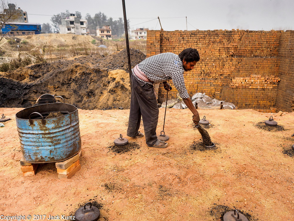 09 MARCH 2017 - BAGMATI, NEPAL: A workers puts coal that fuels the fire into the kiln at a brick factory in Bagmati, near Bhaktapur. There are almost 50 brick factories in the valley near Bagmati. The brick makers are very busy making bricks for the reconstruction of Kathmandu, Bhaktapur and other cities in the Kathmandu valley that were badly damaged by the 2015 Nepal Earthquake. The brick factories have been in the Bagmati area for centuries because the local clay is a popular raw material for the bricks. Most of the workers in the brick factories are migrant workers from southern Nepal.           PHOTO BY JACK KURTZ