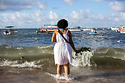 Brazilian woman standing by the sea in contemplation and prayer, making offerings of flowers to Yemanja, the Orixa goddess of the Sea and water.February 2nd is the feast of Yemanja, a Candomble Umbanda religious celebration, where thousands of adherants visit the Rio Vermehlo Red River in Salvador.