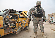 Car that housed a  VBED (Vehicle Borne Explosive Device) that only partialy detonated now at an Iraqi police station where a National Guard inspects the vehicle