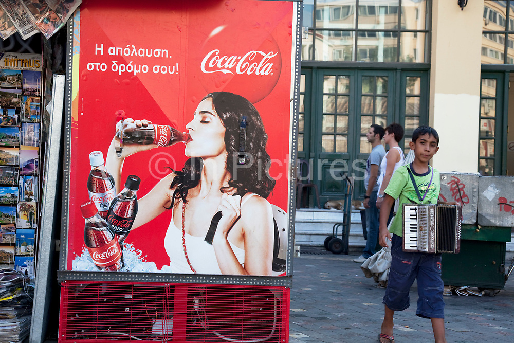 Young boy playing the accordian for money in Monastiraki walks past an aspirational advertisement for Coca Cola. Athens is the capital and largest city of Greece. It dominates the Attica periphery and is one of the world's oldest cities, as its recorded history spans around 3,400 years. Classical Athens was a powerful city-state. A centre for the arts, learning and philosophy.