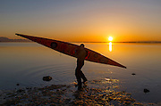 Kayaker comes in at sunset on Dungeness lagoon, inside the Dungeness Spit, on a warm, glassy spring evening—more like summer.