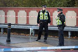 © Licensed to London News Pictures. 10/11/2016. Croydon, UK. Police guard a cordon on the nearest bridge to the tram.  Investigations are continuing into a tram crash that police say claimed seven lives and injured 50. The driver has been arrested and is being questioned by police. Photo credit: Peter Macdiarmid/LNP