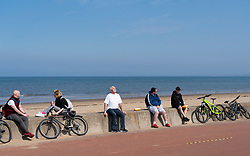 Portobello, Scotland, UK. 25 April 2020. Views of people outdoors on Saturday afternoon on the beach and promenade at Portobello, Edinburgh. Good weather has brought more people outdoors walking and cycling. Police are patrolling in vehicles but not stopping because most people seem to be observing social distancing. People sitting on seawall maintaining social distancing.  Iain Masterton/Alamy Live News