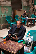 A man reads a book at a table at the Zahrat al-Bustan cafe, Cairo, Egypt