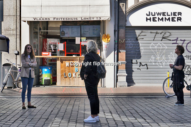 Nederland, Nijmegen, 26-4-2020 De binnenstad van Nijmegen is zo goed als leeg . Het is duidelijk rustiger en stiller in de straten, winkelstraten van het centrum in de stad . Mensen blijven thuis om zo min mogelijk risico te nemen ivm het corona virus . Bij winkels die geopend zijn hebben ondernemers maatregelen getroffen om anderhalve meter afstand te houden . Bij een take away friettent , snackbar .Terrassen zijn gesloten . Foto: Flip Franssen