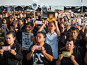 22 NOVEMBER 2016 - BANGKOK, THAILAND:  People hold up photos of the late King of Thailand during a ceremony to honor His Majesty at Sanam Luang Tuesday. Hundreds of thousands of Thais gathered across Thailand Tuesday to swear allegiance to the Chakri Dynasty, in a ceremony called Ruam Phalang Haeng Kwam Phakdi (the United Force of Allegiance). At Sanam Luang, the Royal Parade Ground, and location of most of the mourning ceremonies for the late King, people paused to honor His Majesty by singing the Thai national anthem and the royal anthem.      PHOTO BY JACK KURTZ