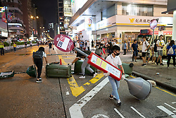 Hong Kong, China. 13th October 2019. Woman suspected of being pro-Beijing is assaulted by pro-democracy protestors in Mongkok district in Kowloon on Sunday evening. This incident was one of several throughout Hong Kong on Sunday which saw acts of vandalism carried out by a minority in the pro-democracy movement. Pic protestors make barricade on Nathan Road .Iain Masterton/Alamy Live News.