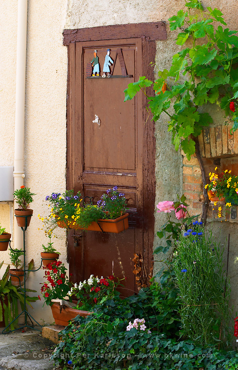 A painted sign that illustrates the theme of champagne and wine production: two people doing remuage (riddling of the bottles) on a brown door profusely decorated with many colourful flowers, the village of Hautvillers in Vallee de la Marne, Champagne, Marne, Ardennes, France