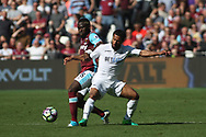 Arthur Masuaku of West Ham United (L) tussling with Wayne Routledge of Swansea City (R). Premier league match, West Ham Utd v Swansea city at the London Stadium, Queen Elizabeth Olympic Park in London on Saturday 8th April 2017.<br /> pic by Steffan Bowen, Andrew Orchard sports photography.