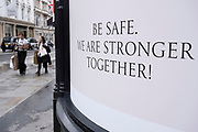 Be safe, we are stronger together sign on Bond Street under coronavirus lockdown on 1st July 2020 in London, England, United Kingdom. As the July deadline approaces and government will relax its lockdown rules further, the central London remains very quiet, while some non-essential shops are allowed to open with individual shops setting up social distancing systems. Bond Street is one of the principal streets in the West End shopping district and is very upmarket. It has been a fashionable shopping street since the 18th century. The rich and wealthy shop here mostly for high end fashion and jewellery.