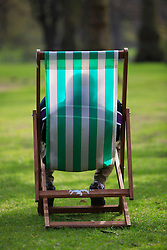 © Licensed to London News Pictures 24/04/2013.A man relaxes in a deckchair whilst enjoying the warm weather and sunshine in St James Park, central London..London, UK.Photo credit: Anna Branthwaite/LNP