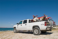 White pickup truck with motorcycles in bed parked near Sea of Cortez, Baja, Mexico