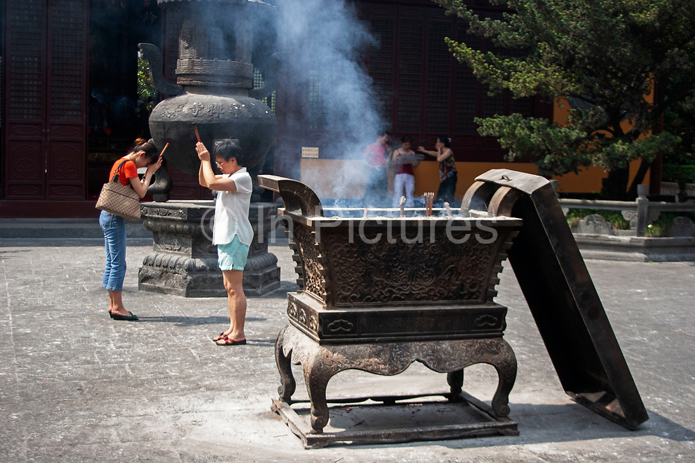 Shanghainese people burn incense during daily prayer sessions at the Longhua Temple in the south of Shanghai, China. This is a working Buddhist temple where public come to burn incense, offer gifts and to eat. Located on Longhua Road, the temple was first built in 242 AD, during the period of the Three Kingdoms. Longhua Temple is the oldest temple in Shanghai and also the largest at 20,000 square metres including it's grounds. Because of several destructions by the wars, most of the buildings in Longhua Temple were reconstructed during the reign of the Emperor Tongzhi and Guangxu during the Qing Dynasty.