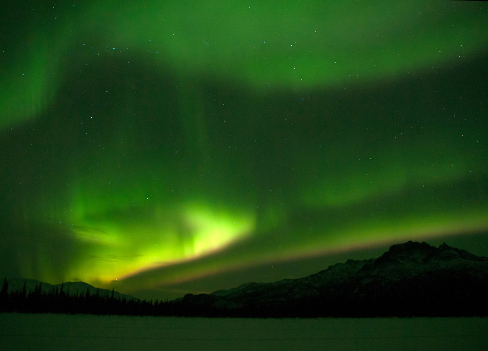 Alaska Range Mountains,  lit up with the Aurora Borealis or Northern Lights in the winter sky.