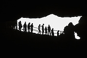 """03 APRIL 2012 - HA LONG, VIETNAM:  Tourists walks in the mouth Hang Sung Sot Cave, also called the """"Grotto Of Surprises,"""" the best explored cave in Ha Long Bay. In 1994 UNESCO declared 174 square miles of Ha Long Bay a World Heritage Site. There are nearly 2000 distinct rock islands in the bay, which for centuries has been the home to isolated fishing villages. Now thousands of tourists stream through the bay and around the islands every day on cruise ships. On the Vietnamese mainland, around the town of Ha Long, real estate companies are developing exclusive condominium and apartment complexes for use as weekend homes for people in Hanoi, about a 3.5 hour drive from Ha Long.    PHOTO BY JACK KURTZ"""