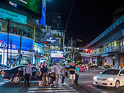 02 SEPTEMBER 2013 - BANGKOK, THAILAND: People wait in the middle of Ratchadaphisek for the light to change so they can cross where it intersects with Sukhumvit Road. It is a popular tourist and shopping destination. Terminal 21 and Soi Cowboy entertainment district are in the neighborhood.       PHOTO BY JACK KURTZ