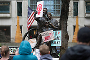 A group in the  Women's March on Portland takes photos of a decorated pioneer statue in downtown Portland on Saturday, Jan. 21, 2016. The march was held in support of a national women's march held in Washington, D.C.  Photo by Randy L. Rasmussen, © 2017.
