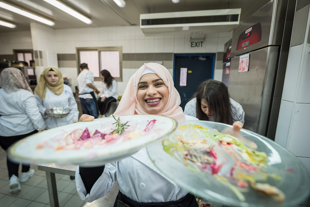 25 February 2020, Jerusalem: Sara Ewiwe from 'Anata holds up two well-eaten plates ready to be washed, as she participates in catering class at the vocational training centre in Beit Hanina. The Lutheran World Federation's vocational training centre in Beit Hanina offers vocational training for Palestinian youth across a range of different professions, providing them with the tools needed to improve their chances of finding work.