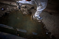 cuban man running through puddle in havana