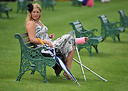 © licensed to London News Pictures. ASCOT, UK.  16/06/11. A young lady in a pink plaster cast sites on a bench at Royal Ascot. Ladies Day at Royal Ascot 16 June 2011. Royal Ascot has established itself as a national institution and the centrepiece of the British social calendar as well as being a stage for the best racehorses in the world. Mandatory Credit Stephen Simpson/LNP