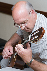 Man playing a guitar at Age Concern local talent show,