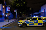 A Met Police officer at the closed-off roads surrounding Herne Hill and Carnegie Library in Lambeth, after two people were reported shot in this residential south London road, on 10th September 2020, in London, England. The two victims were taken to hospital with non-life threatening injuries.