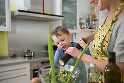 Boy helping his mother to pepper salad