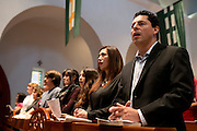 Juan Enriquez sings hymns with his family during mass at St Ann Catholic Parish in Coppell, Texas on October 12, 2014. (Cooper Neill for The New York Times)