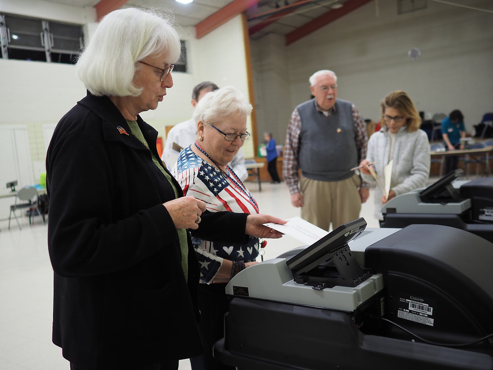 Arlington, VA election officials check the optical scanner prior to opening the polls on Presidential Primary Day.