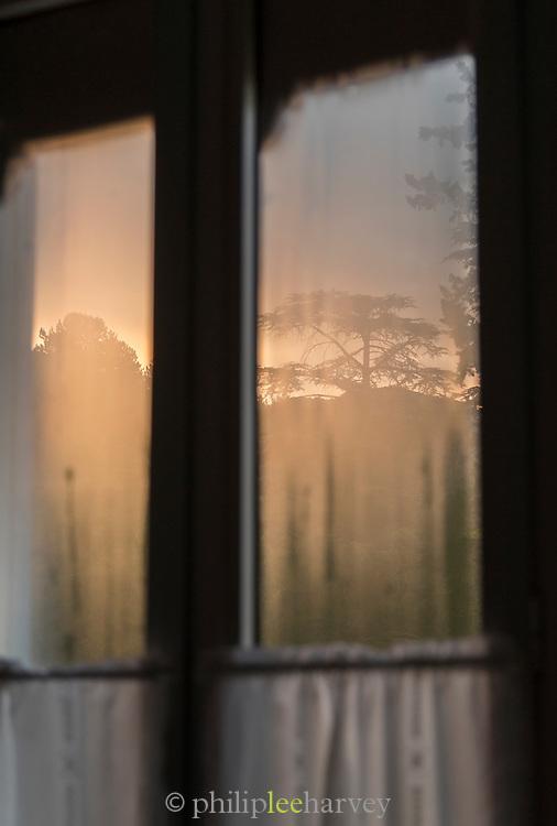Misty window with net curtain at dusk, Sisteron, France