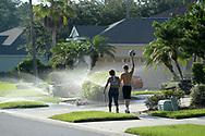 A couple walk through sprinklers in the Hunter's Creek neighborhood in Orlando, Fla., Monday, Aug. 22, 2016. (Phelan M. Ebenhack via AP)
