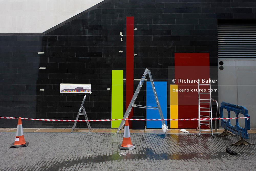 London's Southbank Festival of the World designs being stuck to concrete underpass wall.