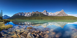 Upper Waterfowl Lake Panorama.  A bluebird day reflects the towering Canadian Rockies into the still water of this incredible lake along the Icefields Parkway in Banff National Park.