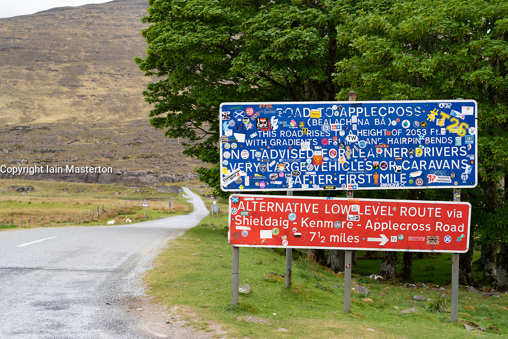Warning signs covered in drivers' stickers at base of the Bealach na Ba pass on Applecross Peninsula on North Coast 500 scenic driving route in Scotland, UK