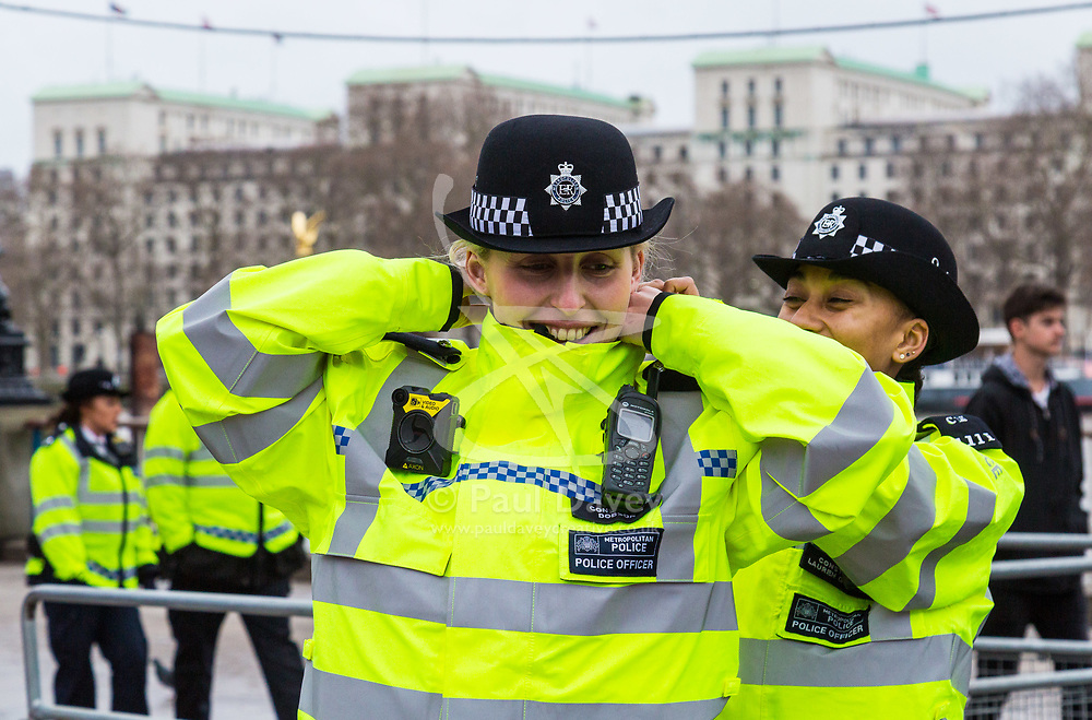 London, December 31 2017. Police in high visibility jackets and numerous anti-terrorism and crowd control measures are in place in the capital ahead of the New Year's Eve fireworks and revelry in central London. PICTURED: A police officer fixes her colleague's collar on Southbank. © SWNS