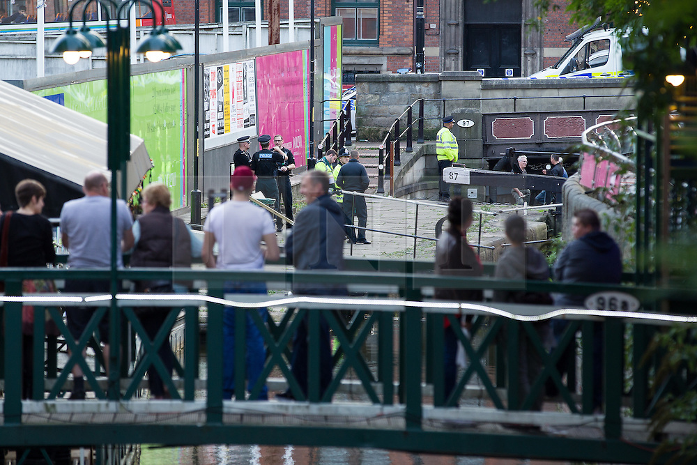 """© Licensed to London News Pictures . Manchester , UK . FILE PICTURE DATED  06/10/2013 of onlookers watching as police drain a lock in Manchester City Centre , to recover a body . Police pulled a body from The Bridgewater Canal in Manchester , adjacent to the City's """" Gay Village """" on Canal Street . Greater Manchester Police have issued a statement after suggestions that a number of deaths in and around Manchester's canals may be linked to a serial killer , named in local folklore as """" The Pusher """" . The statement said """" Absolutely no evidence whatsoever of foul play has been established """" . Photo credit : Joel Goodman/LNP"""