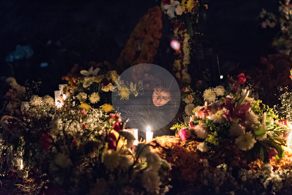A young girl lights a candle at the Tzurumutaro cemetery during the Day of the Dead festival November 2, 2017 in Patzcuaro, Michoacan, Mexico.  The festival has been celebrated since the Aztec empire celebrates ancestors and deceased loved ones.