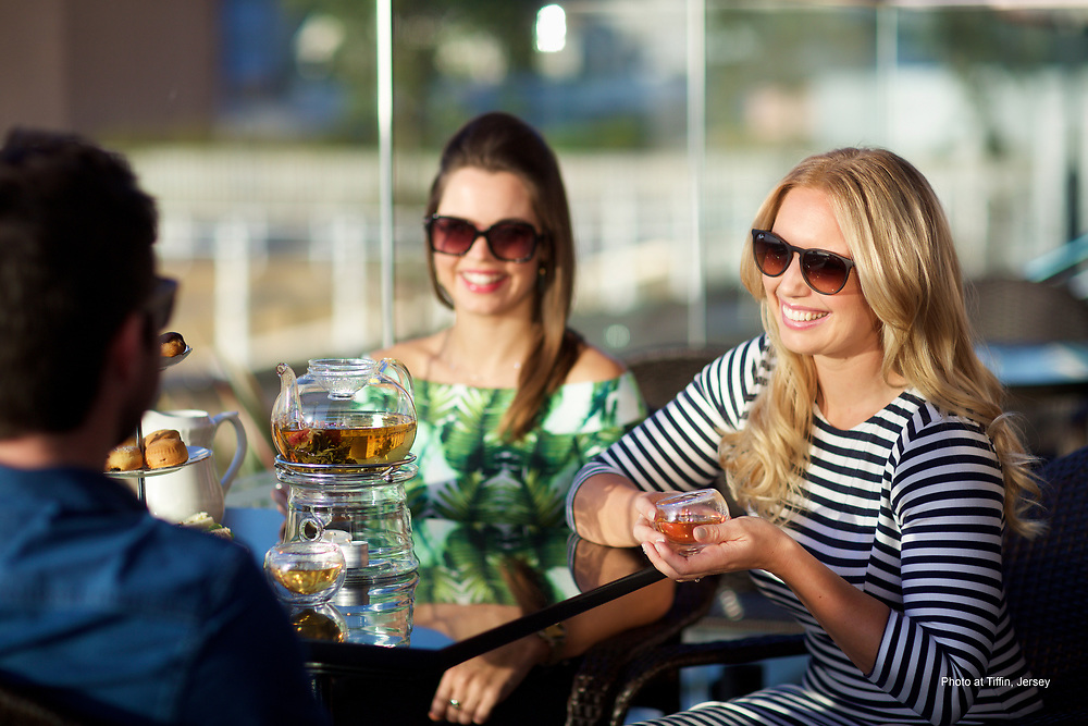 Friends eating, drinking and socialising with afternoon tea at Tiffin bar and restaurant along the waterfront of Jersey, CI