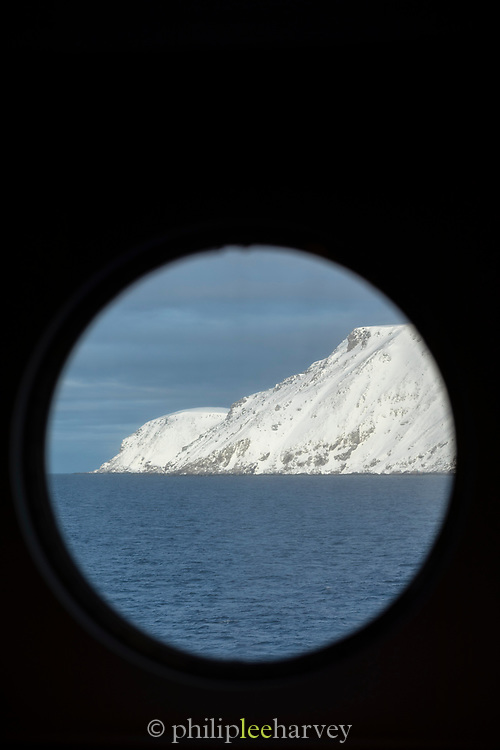 Scenic winter landscape of mountain seen through window in ship cabin, Havoysund, Norway