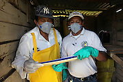 """Wilfrido Medina (right), 32, BSCFA Environmental Field Officer, and Frejedes Catch, 41, from Xaibé, review Mr. Catch's warehouse inventory sheet inside his storage room. Mr. Catch, who has been growing sugar cane for 26 years, declares: """"Fairtrade has helped us a lot. It has provided monetary aid for our children who study. Also, the Fairtrade standards have helped improve our environment as less people have been intoxicated by following the improved storage regulations. Also, there is less plastic on the sugar cane fields. Many of us were not conscious of the secondary problems caused by pollution."""" Belize Sugar Cane Farmers Association (BSCFA), Xaibé, Corozal, Belize. January 22, 2013."""