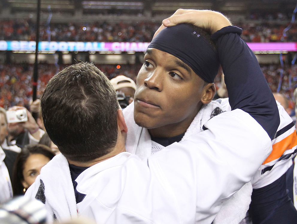 ATLANTA - DECEMBER 4:  Head coach Gene Chizik of the Auburn Tigers (left) hugs quarterback Cam Newton #2 after the 2010 SEC Championship against the South Carolina Gamecocks at Georgia Dome on December 4, 2010 in Atlanta, Georgia. The Tigers beat the Gamecocks 56-17.  (Photo by Mike Zarrilli/Getty Images)
