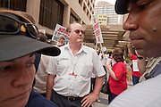 """19 JUNE 2009 -- PHOENIX, AZ: Phoenix police officers (foreground) watch a man who had been trying to shout down anti-sheriff protestors during a demonstration against Maricopa County Sheriff Joe Arpaio at the Wells Fargo Bank building Friday. The Sheriff's Department is headquartered in the Wells Fargo Bank building. Rev. Al Sharpton was in Phoenix Friday to protest the high profile """"crime suppression"""" sweeps conducted by the Sheriff's Department. Critics contend the sweeps use racial profiling to target Hispanics. PHOTO BY JACK KURTZ"""